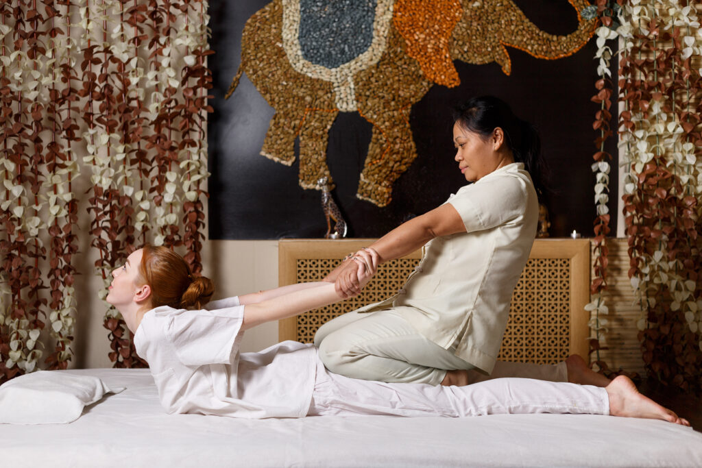 Frau massiert Kundin mit traditioneller Thai Massage